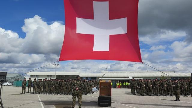 Schweizer Fahne und Soldaten auf Flugplatz.