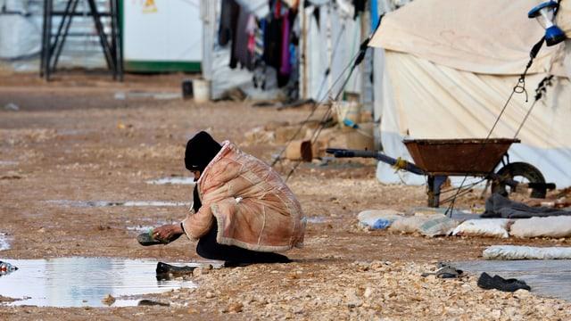 Eine Frau im Lager Zaatari wäscht ihre Schuhe in einer Pfütze.
