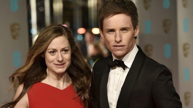 Frau in rotem Kleid neben Mann mit schwarzem Jackett.