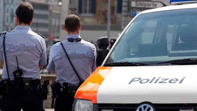 Zwei Zürcher Stadtpolizisten stehen neben einem Polizeiauto