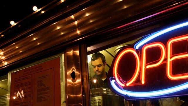 Ein Mann steht am Fenster eines Diners mit einem Leuchtschild im Fenster.