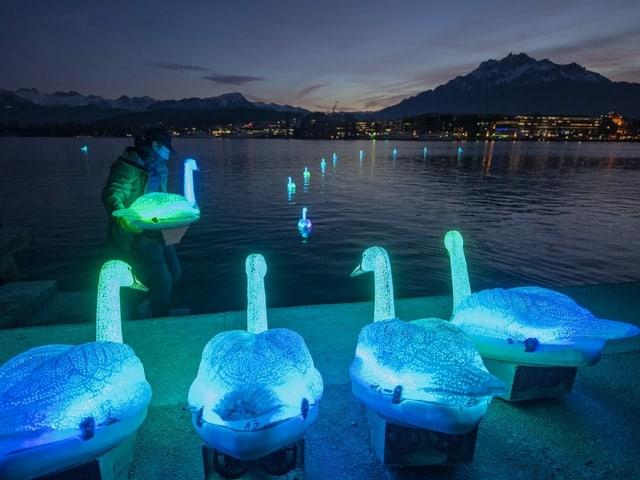 Imposante Kunstinstallation auf dem See mit künstlich leuchtenden Schwänen