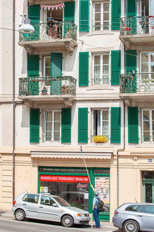 Ein Mann steht auf einer Strasse und streckt ein Teleskop-Mikrophon in Richtung einer Frau auf einem Balkon im zweiten Stock.
