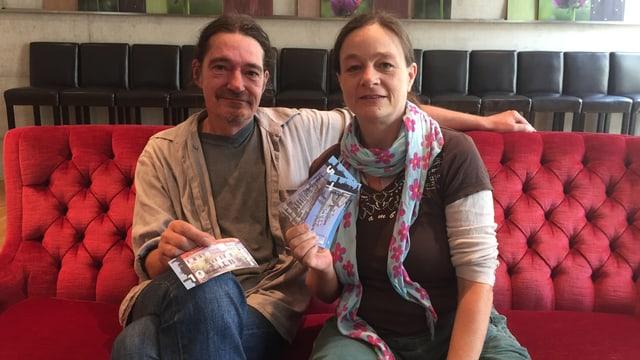 Ein Mann und eine Frau sitzen auf einem Sofa. Beide halten sie je einen Geldschein in der Hand. Es sind die Eulachtaler.