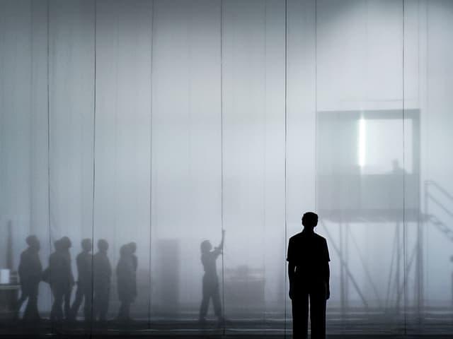 Theaterszene: Menschen auf einer Bühne im Nebel.
