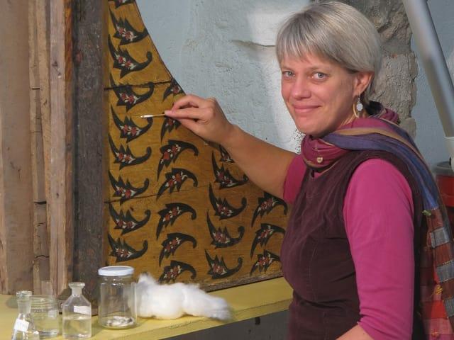 Eine Frau vor einer Wand mit Mustern