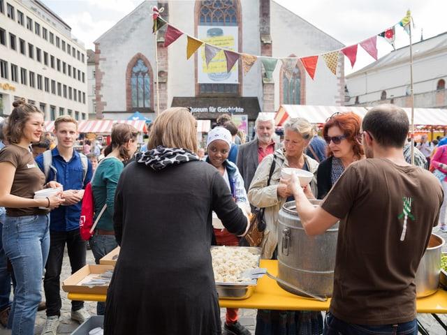 Leute stehen an am Stand von Foodsharing Basel und warten auf Essen.