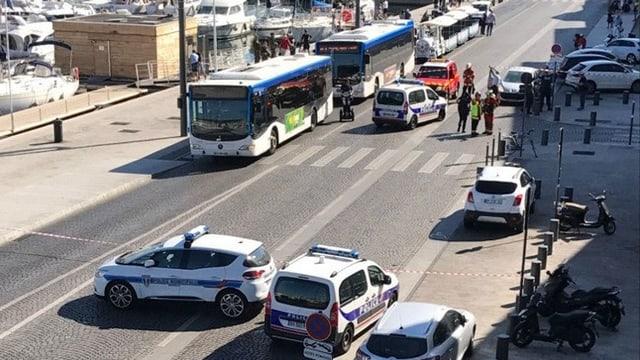 plirs autos da polizia èn sa fermads avant ina fermada da bus