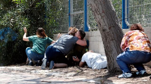 Menschen knien und ducken sich hinter einer Mauer.