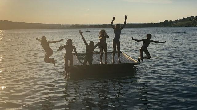 Kinder springen von Floss.