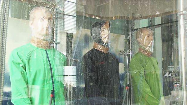 Drei Puppen mit Softshell-Jacken sind künstlichem Regen ausgesetzt.