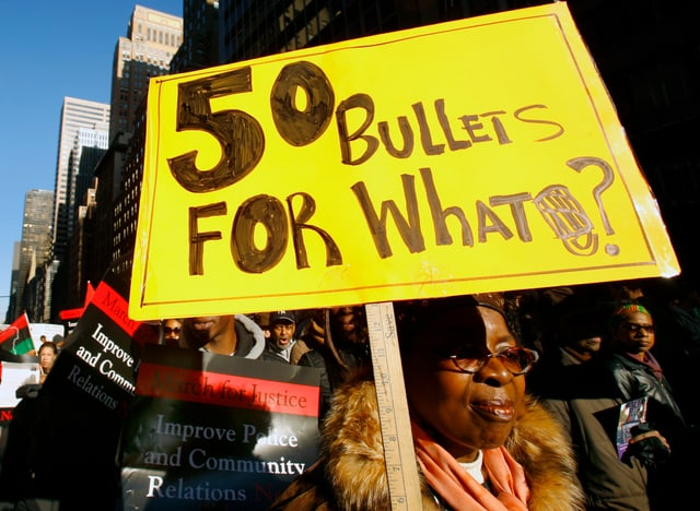 Eine Frau hält ein gelbes Schild mit der Aufschrift «50 Bullets for what?»