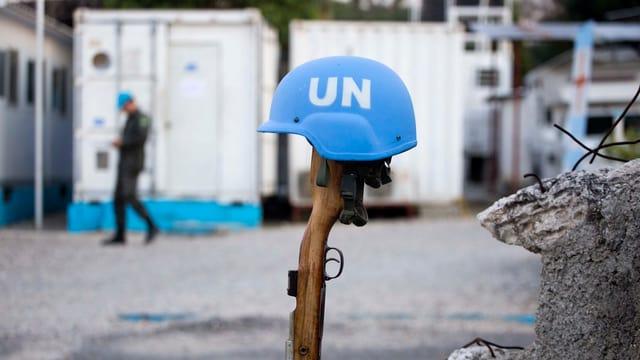 Ein blauer Helm auf einem stehenden Gewehr.