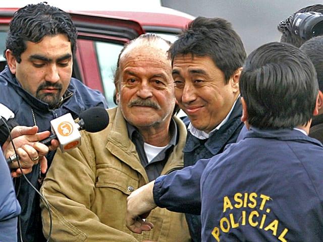 2007: Ex-General Raul Iturriaga ist in Santiago, Chile, von Polizisten umringt. Ein Journalist hält ihm ein Mikrophon vor den Mund.