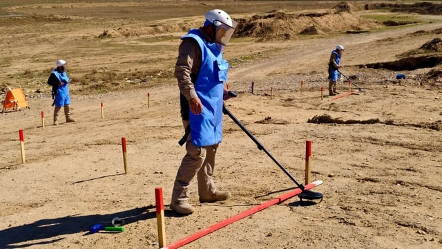 Minenräumer mit Helmen und Westen suchen mit Detektoren markierte Flächen ab.