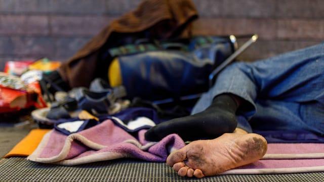 Obdachloser liegt mit Kleidern am Boden in einer Stadt