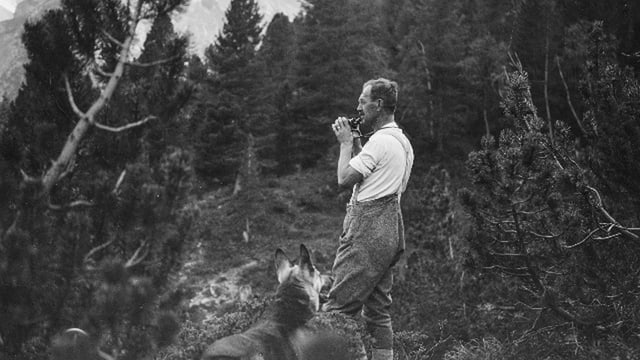Hermann Langen steht mitten im Wald, ein Fenrglas halb zu den Augen gehoben und schaut angestrengt in die Ferne. Am unteren Bildrand schaut sein Schäferhund zu ihm auf.
