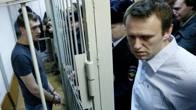 Oleg Nawalny hinter Gittern, Alexej davor, rundherum Leute.