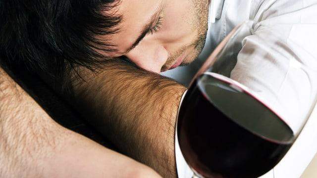 Junger Mann schläft neben einem Glas Rotwein