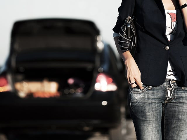 Frau telefoniert vor Auto mit Panne