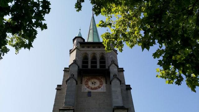 Durch Ahornblätter hindurch ist ein Kirchenturm mit rot-goldenem Ziffernblatt zu sehen.