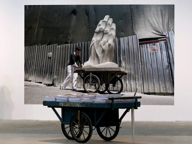 Ein Karren voll Bücher steht vor einem Gemälde, das einen Karren mit einer überdimensional grossen Hand zeigt.