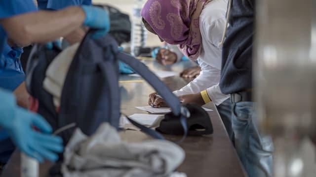 Gepäck von Flüchtlingen wird am Grenzübergang in Chiasso durchsucht.