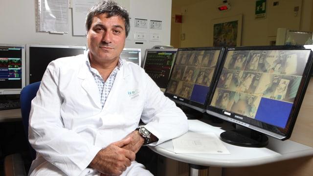 Ein Arzt im weissen Kittel sitzt am Schreibtisch.