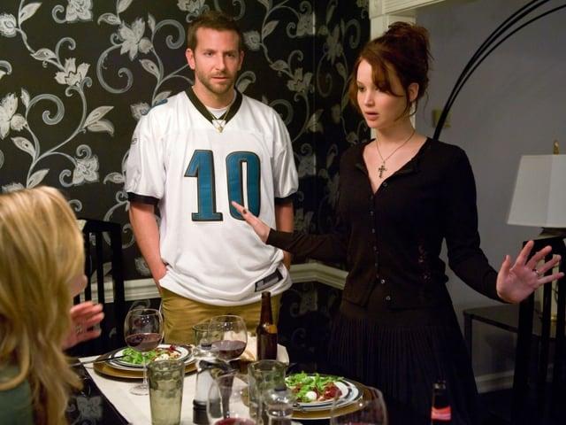Bradley Cooper und Jennifer Lawrence in einer hitzigen Diskussion bei einem Abendessen mit einer blonden Frau.