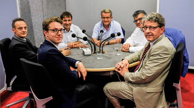 Ils presidents da las partidas a la maisa da discussiun en il studio.