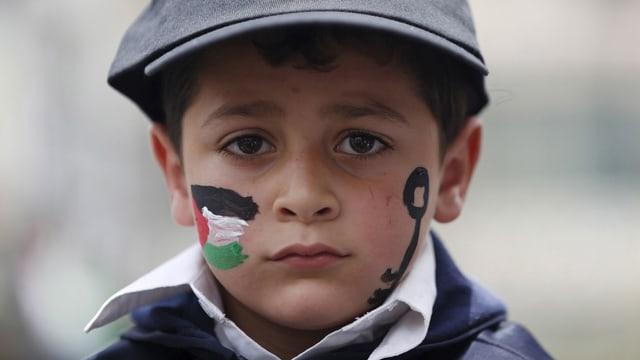 Ein Junge mit ausfgemalter Pälastina Flagge und Schlüssel.