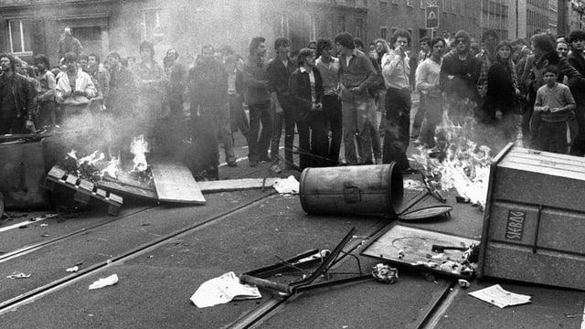 In einer s/w-Aufnahme stehen Jugendliche auf der Strasse neben brennenden Containern und umgekippten Abfalleimern.