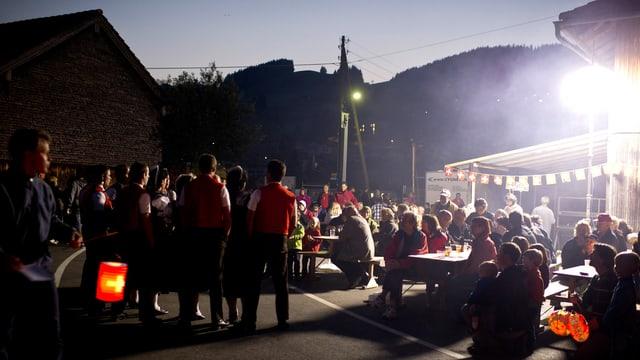 1.-August-Feier in der Nacht mit vielen Leuten, Lampions und Fähnchen.