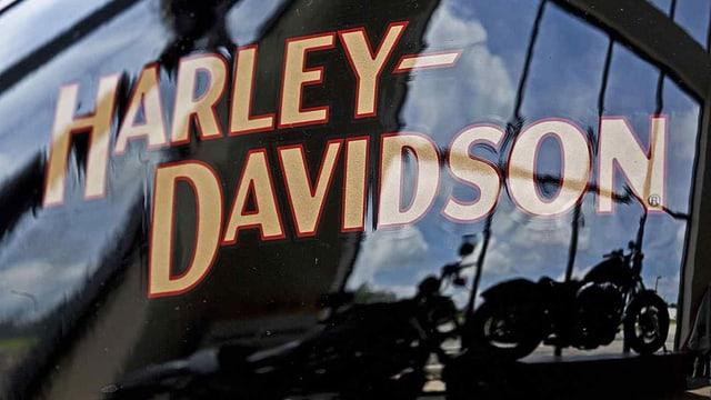Harley-Davidson Schriftzug auf einem Tank, darin spiegelt sich ein Motorrad