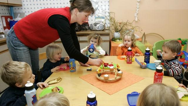 Ein Tisch mit Kindern, eine Betreuerin.
