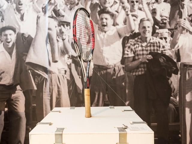 Tennisraket steht auf Ausstellungstisch, im Hintergrund sieht man jugendle Sportfans auf einem Foto.