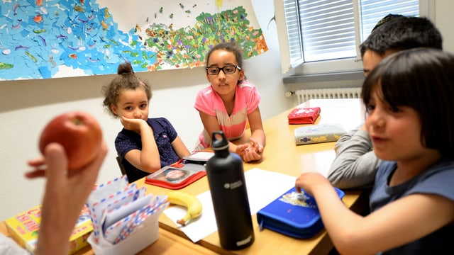 Eine Lehrerin zeigt ausländischen Kindern einen Apfel.
