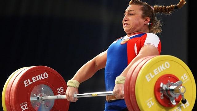 Eine Russin hebt ein Gewicht auf.