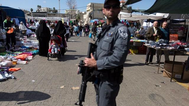 Ein Bewaffneter steht auf einem Marktplatz