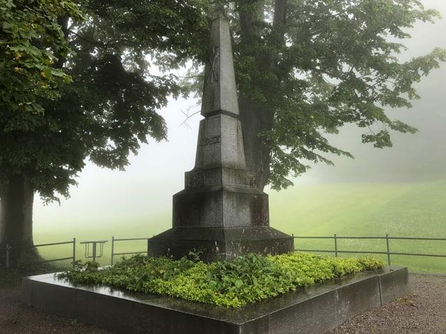 Ein Steindenkmal unter einem Baum.
