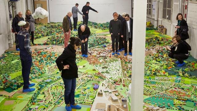 buntes Stadtmodell in einem grossen Raum, darauf stehen Leute
