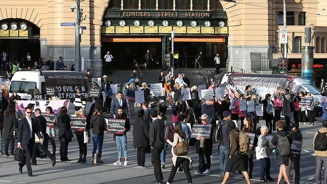 Personen mit Plakaten vor einem Jugendstil-Gebäude.