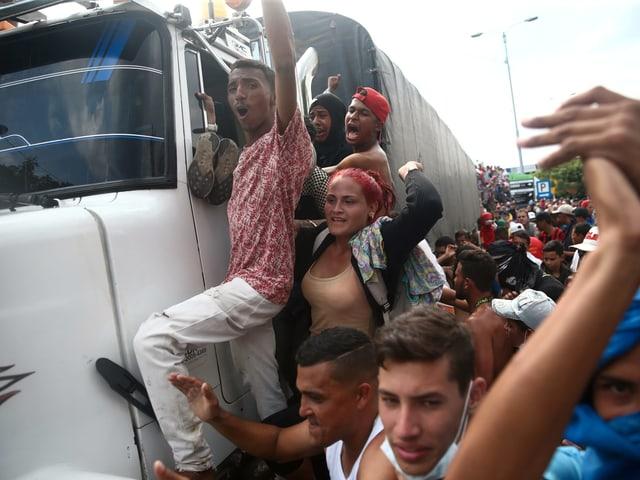 Demonstranten hängen sich an einen Lastwagen.