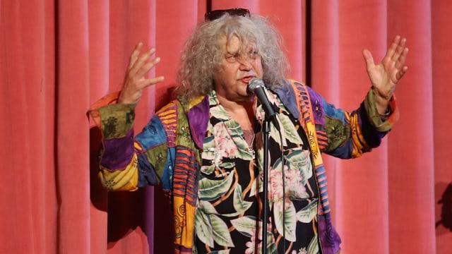 Dicker alter Mann spricht auf einer Bühne in ein Mikrofon und gestikuliert mit den Händen.