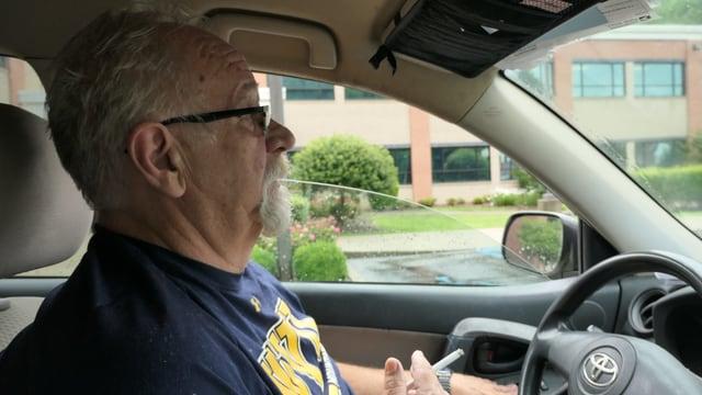 Gary Ball sitzt rauchend in seinem Auto.