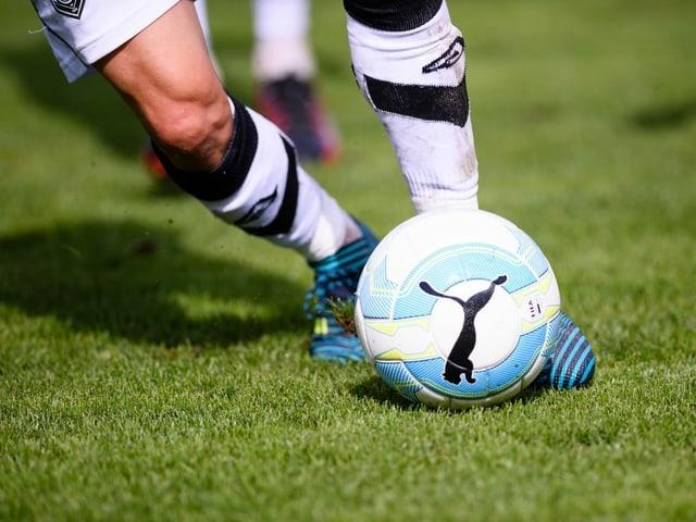 Grossaufnahme eines Fussballes, der getreten wird.