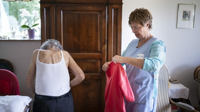 Spitexmitarbeiterin hilft einer alten Frau