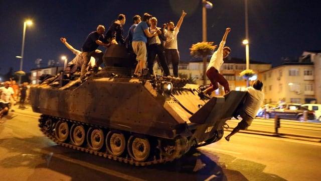 Personen auf einem Panzer.