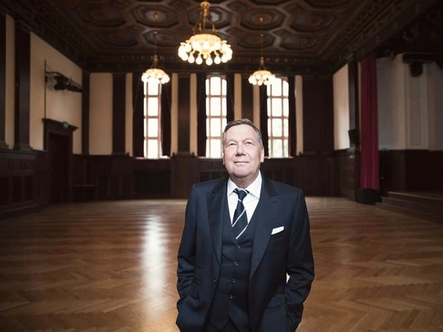 Mann steht in grossem Saal mit Parkett, Kronleuchtern und roten Vorhängen.