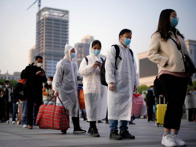 Menschen mit Gepäck stehen Schlange für die Ausreise